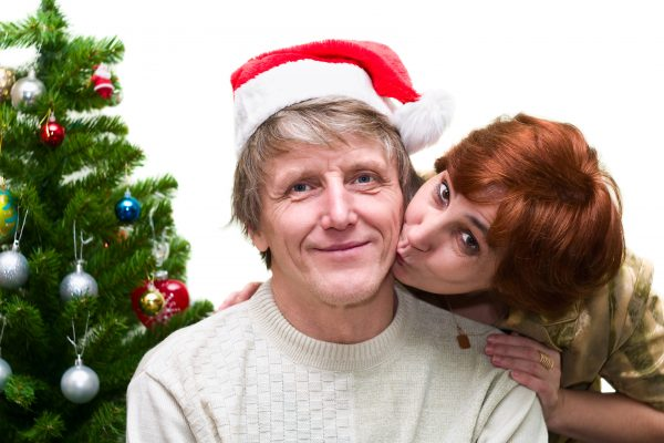 Mature woman kissing a old husband near the Christmas tree. Loving senior couple on white background