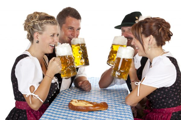 Bavarian men and women drink cheerfully Oktoberfest beer stein. Isolated on white background.