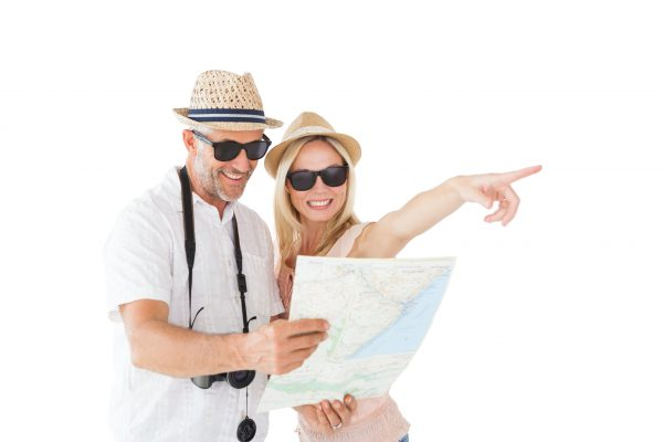 Happy tourist couple using map and pointing on white background