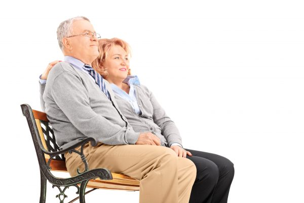 Senior couple hugging and looking in the distance seated on a bench isolated on white background