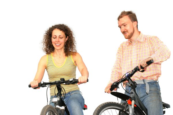 Pretty woman and young man on a bicycles isolated over a white background