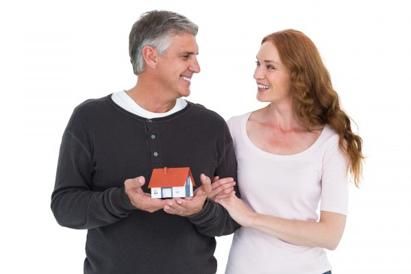 Casual couple holding small house on white background
